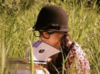 Girl with spectacles and cloche hat sitting in a field and reading intently
