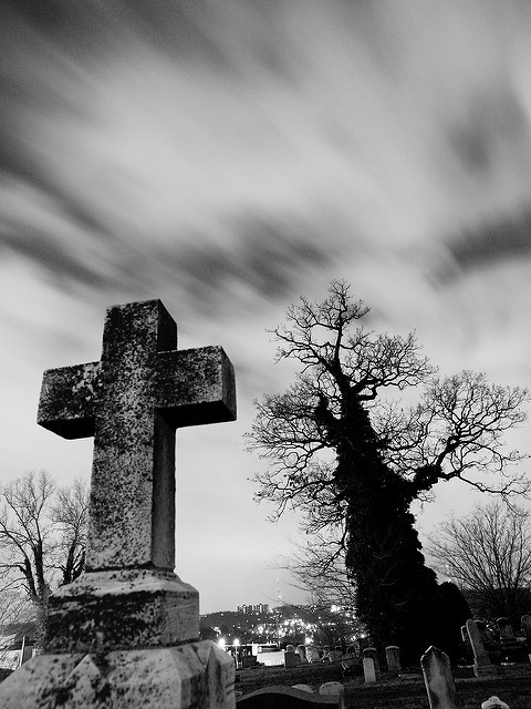 Stone cross on tomb with bare tree behind against a cloud-swept sky. Photo by Bill Mill.