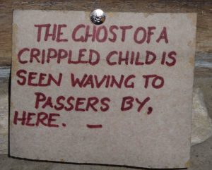 Handwritten sign about the ghost of a crippled child