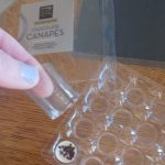 Thumb and forefinger holding plastic casing that surrounds a single Moser Roth chocolate canape