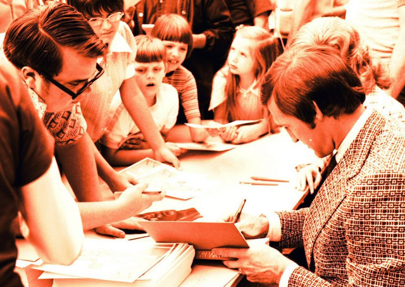 1960s-era scene with male author signing a book while people including children queue