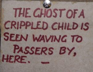 "Red writing saying: ""The ghost of a crippled child is seen waving to passers by here."""