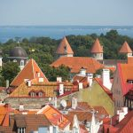 The red rooftops of Tallinn with trees and sea behind