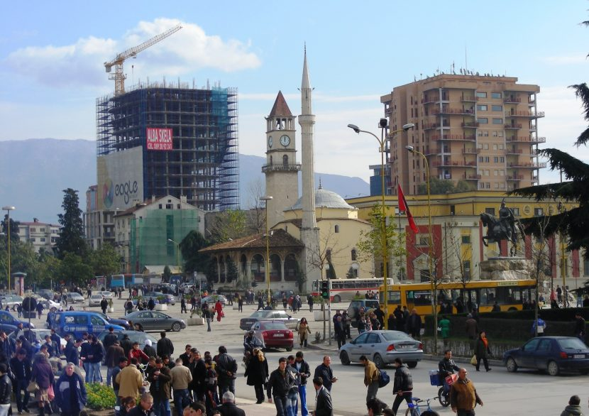 A mosque, Soviet style building and a crane with lots of men in the foreground: Tirana