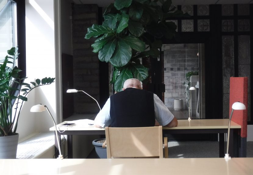 Rear view of man reading at a library desk