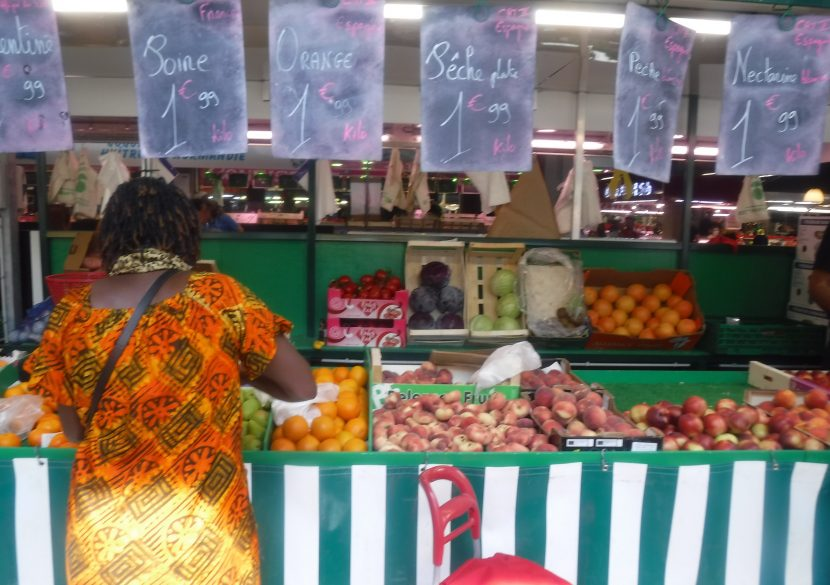 Rear view of woman shopping at a fruit and veg stall in a French market